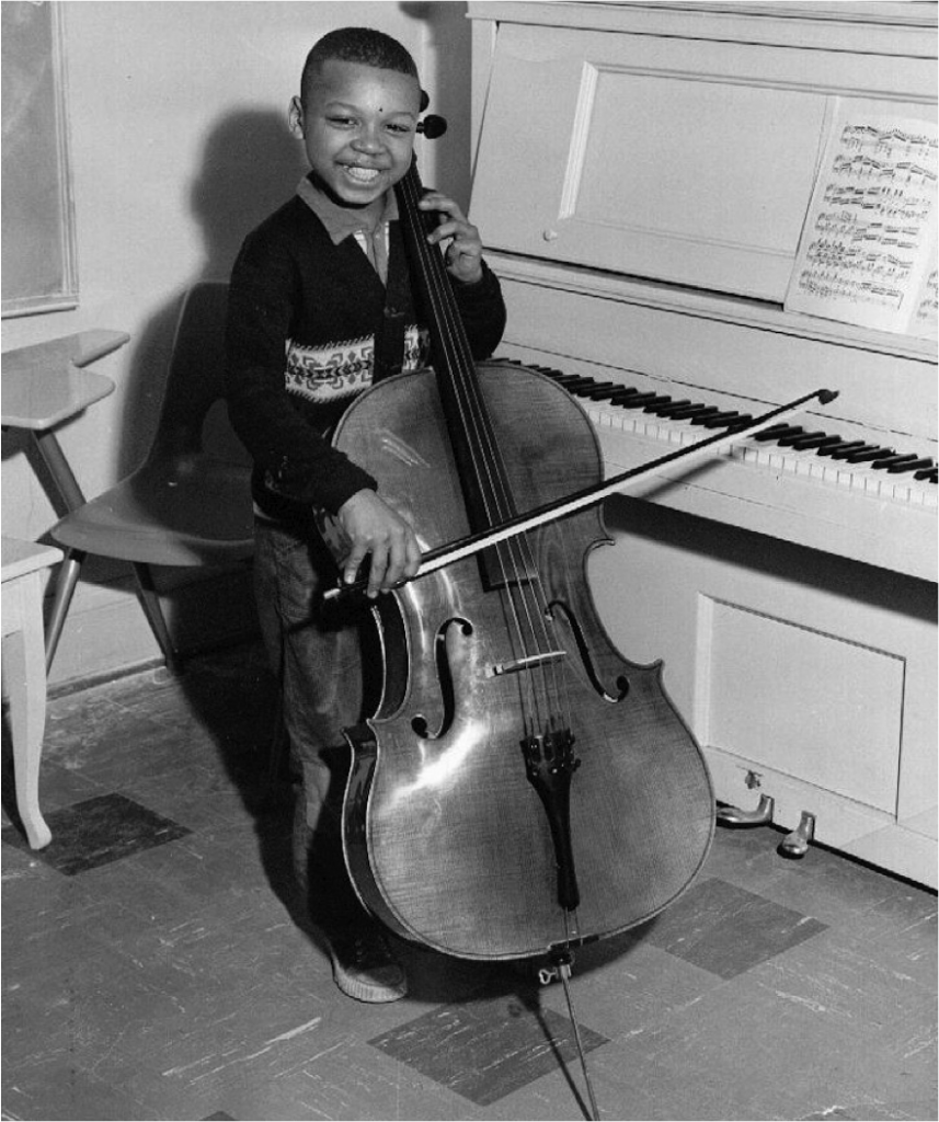 Black and white photo of little boy playing cello in the St. Christopher House Music School