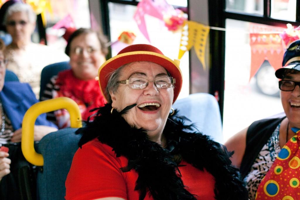 Female Senior laughing on bus