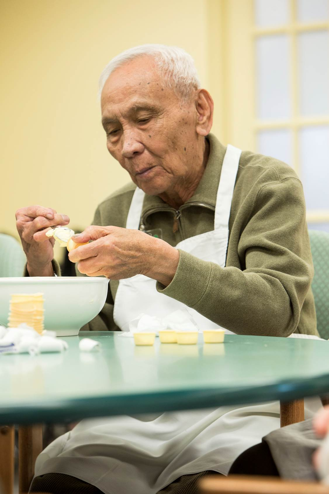 Participant in an Adult Day Services program doing some baking